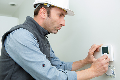 Furnace repairman adjusting HVAC thermostat for maintenance